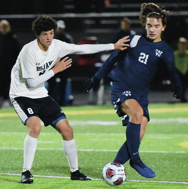 Botkins' Nathan Schneider, left, jostles for ball control with Wellington's Henry Lin during a Division III state semifinal on Wednesday at Springfield High School Stadium.