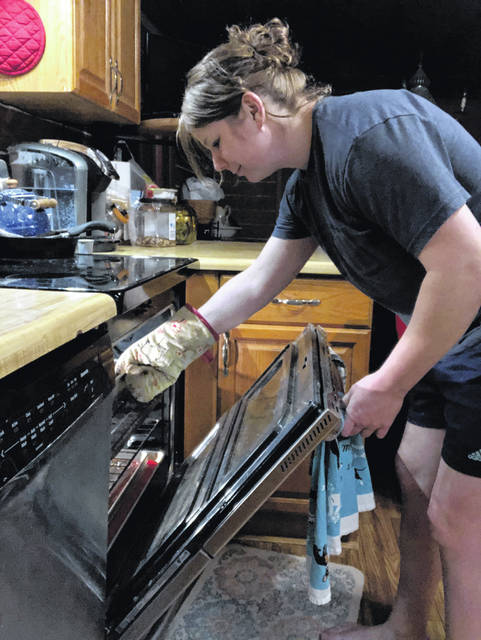 Shannon Boyer, of Anna, checks the oven to see if her latest creation is done.