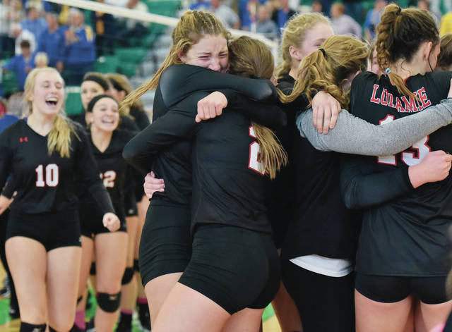 Fort Loramie's McKenzie Hoelscher hugs Marissa Meiring as other players celebrate following the team's win over Russia in a Division IV regional final on Saturday at Northmont High School's Thunderdome.