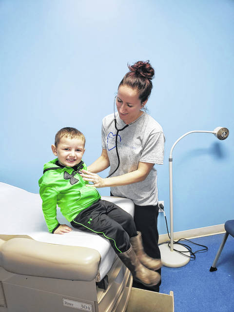 Stacey Robinson, a certified nurse practitioner, checks out a young Compassionate Care patient. Match Day offsets the cost of two nurse practitioners.