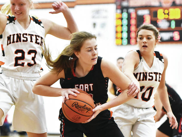 Fort Loramie's Ava Sholtis fends of Minster's Ella Mescher, right, and Mara Schmiesing during a nonconference game on Saturday night in Minster. Sholtis led the Redskins with 10 points.