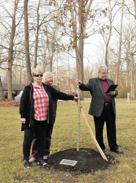 A red oak tree is dedicated to the memory of Thomas M. Ferguson Jr. and Murray C. Ferguson II . Standing, left to right, are Linda Steenrod, Cathy Schmidt, sisters of Thomas M. Ferguson Jr. and Murray C. Ferguson II, and Phil Chilcote, who officiated the dedication in Tawawa Park Wednesday afternoon.