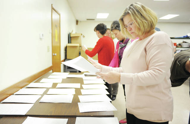 Shelby County Historical Society President Julie Gilardi looks over results.