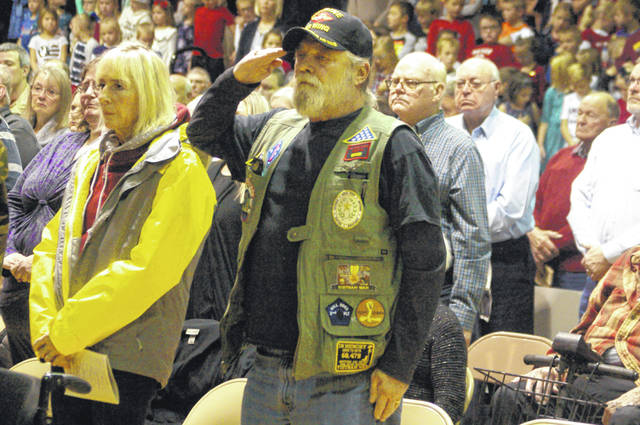 "Mark Jackson, of Coldwater, who served in the Marine Corps during the Vietnam War, salutes during the playing of ""Taps"" during an assembly Monday morning at New Bremen Elementary/Middle School."