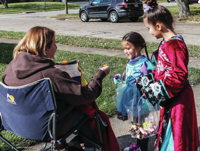Megan Davis, left to right, hands Kimber Farris, 5, and her sister Alanna farris, 7, all of Sidney, daughters of Briana Farris, candy during trick-or-treat in Sidney on Saturday, Nov. 2.