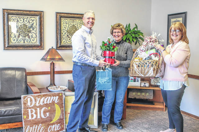 Peggy Ware, center, of Jackson Center, was the winner of the Shop Hop event, which was sponsored by Angels in the Attic Craft Show, Sidney Visitors Bureau, Sidney Alive and the Sidney-Shelby County Chamber of Commerce. Presenting Ware with her prizes are Jeff Raible, left, president of the Sidney-Shelby County Chamber of Commerce, and Darla Cabe, right, Angels in the Attic organizer. The event was held Nov. 6-9 and the grand prize was worth $500.