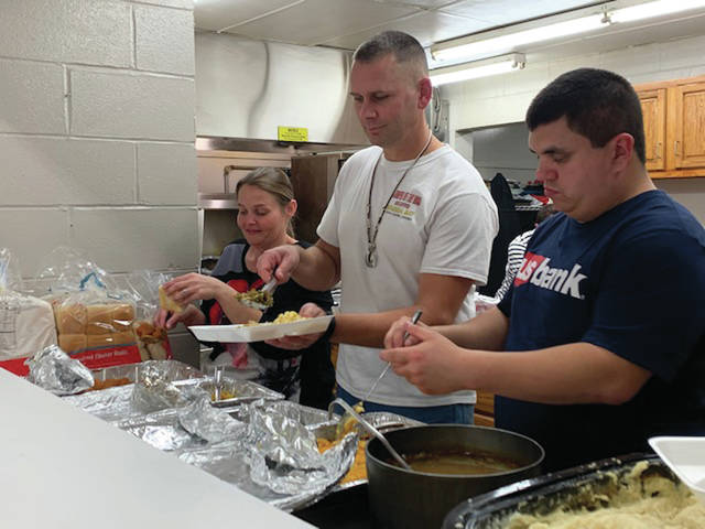 Volunteers, left to right, Crystal Shoe, Justin Neu and Ryan Krivacek, of Sidney, dish food during the Alpha Community Center thanksgiving dinner on Friday, Nov. 22.