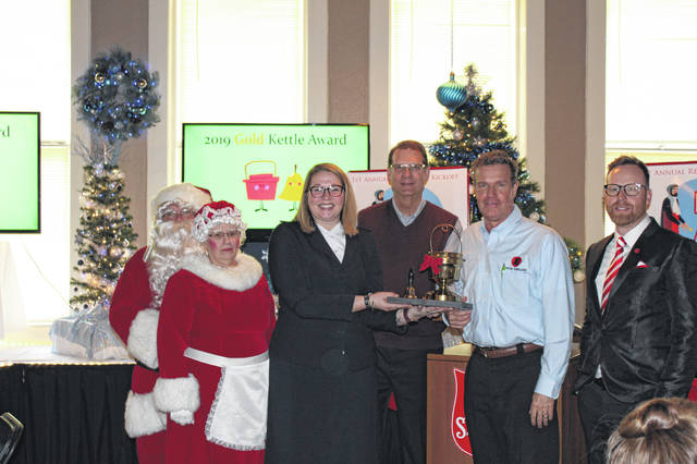 Everyday Technologies Inc. won the first Gold Kettle Award during the 2019 Red Kettle Kickoff. Shown, left to right, are Santa and Mrs.. Claus, Lt. Katie Mayes, Salvation Army Advisory Board member Wayne Thompson, Bruce Toal of Everyday Technologies Inc., and Ryan Ray, Salvation Army development director.