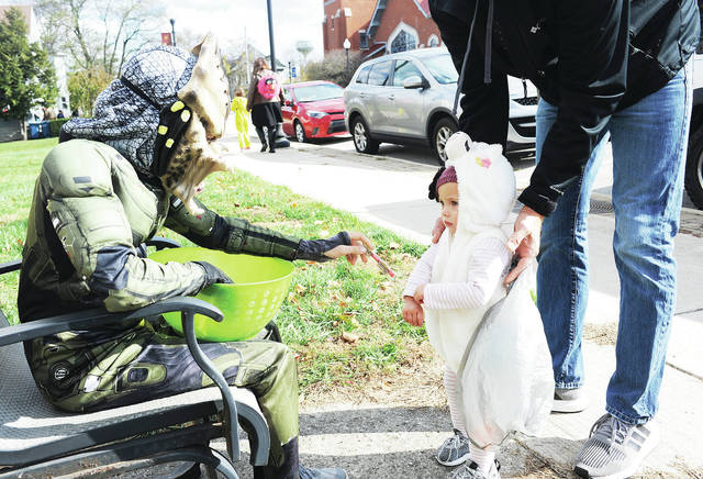 Rylan Egbert, left, 13, offers candy to Evelyn Frilling, 1, who was trick-or-treating with her dad, Brian Frilling, all of Anna, in Anna on Sunday, Nov. 3. Evelyn is also the daughter of Christina Frilling.