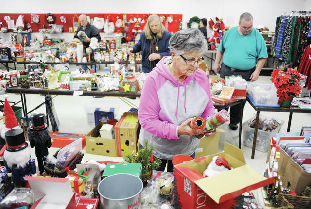 Carol Dunkel, of Russia, sets out Christmas decorations during FISH's Christmas Store season opening on Saturday, Nov. 2. The store is located at 1126 W. Michigan Street.