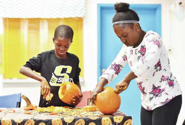 Yaya Sow, left, 9, and his sister Hapsa Sow, 10, both of Sidney, children of Aichata Louzolo, carve pumpkins during the Sidney-Shelby County YMCA Before and After School Program on Friday, Nov. 1. Yaya was not a fan of the pulp that he had to remove from the pumpkin.