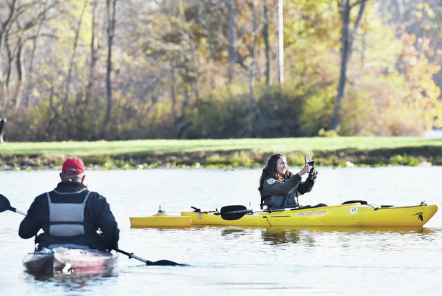 "Ohio Department of Natural Resources Naturalist Richelle Gatto, right, of Berlin Center, takes video of herself on Lake Loramie for her blog on Sunday, Nov. 4. Paddling out to Gatto is Lake Loramie Improvement Association President Leon Mertz, of Minster. Lake Loramie State Park was the 31 stop on a 10 day trip for Gatto to see all 75 Ohio state parks. Gatto spent 30 minutes at each park. She was impressed with the handicap accessible boat launch she had a chance to use at Lake Loramie. Gatto said of the boat launch ""I want one in every single park."""