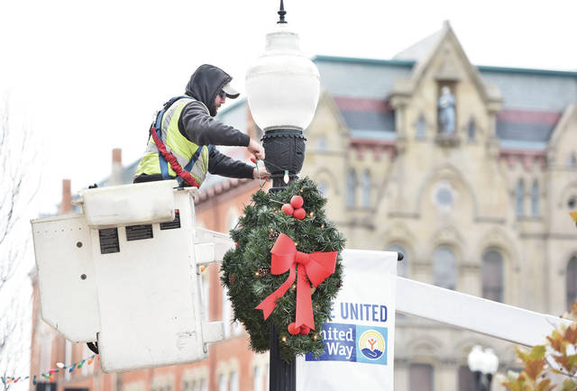 City of Sidney employee John Smith, of Fort Loramie, hangs Christmas lights along Court Street on Monday, Nov. 4.