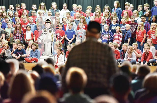Members of the U.S. Coast Guard stand as Anna Elementary students sing the official Coast Guard song during the Anna Elementary Veterans Day program on Monday, Nov. 11. The children sang for each branch of the U.S. military.