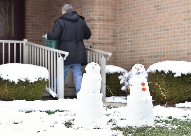 Ed Snyder walks behind snowmen on Wednesday, Nov. 13, that his grandchildren Ben, 7, and Abby Snyder, 5, made on Tuesday, Nov. 12, in front of Snyder's house on Hoewisher Road in Sidney.