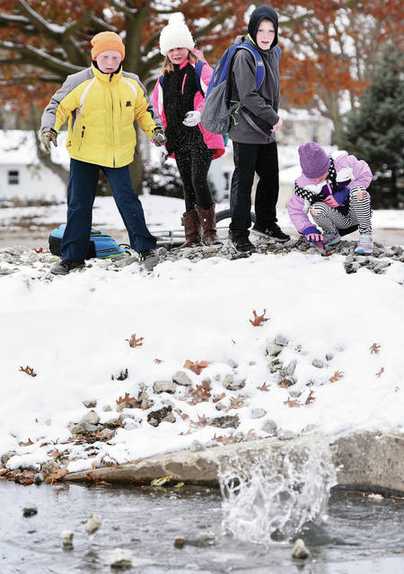 Throwing rocks through the ice in the New Bremen canal along East Plum Street after school on Wednesday, Nov. 13, are, left to right, Ben Craft, 11, his sister Brooke Craft, 9, the children of Shannon and Brad Craft, Will Elshoff, 9, son of Tess Elshoff and Chad Elshoff, and Kennedy Trego, 8, all of New Bremen, daughter of Jodi and Bryan Trego.