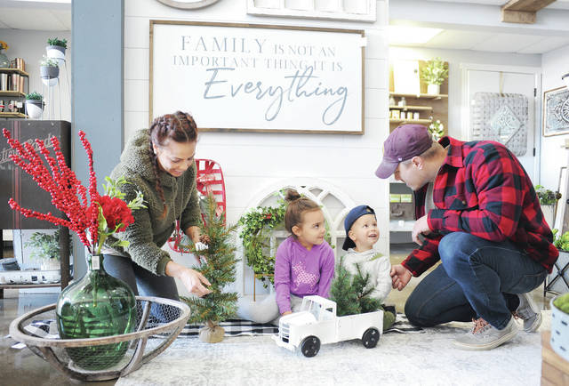 Getting the family business, 937 Designs, ready for Christmas on Friday, Nov. 15, are, left to right, Gretchen Billing, her children Pascale Billing, 5, Ludwin Billing, 2, and her husband, Logan Billing.