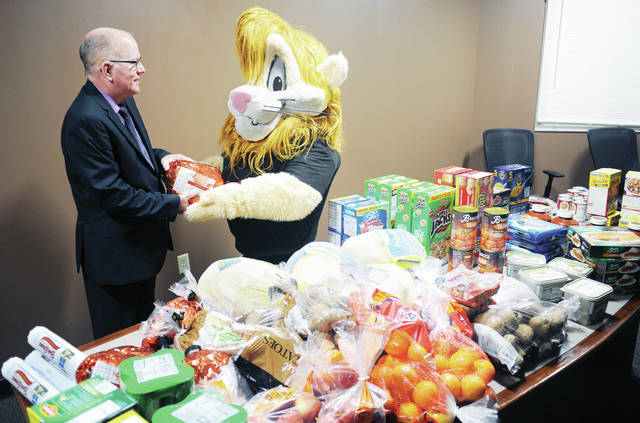 Chief Deputy Jim Frye, left, is handed a ham by Darren the DARE Lion at the Shelby County Sheriff's Office on Wednesday, Nov. 27. The ham is one of four bought to give to families in need.