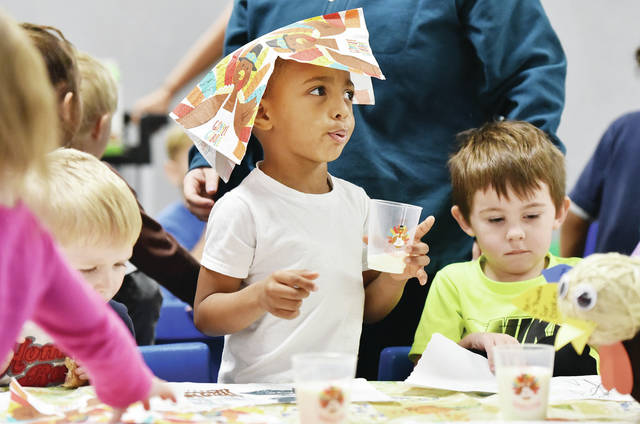 Kyren Huckleby, center, 4, son of Kiara Smith and Michael Huckleby, wears his napkin for a hat while eating a Thanksgiving dinner for preschool students at the Sidney-Shelby County YMCA. Sitting next to Kyren is Jaxin Matthieu, left, 4, son of Janice Bertsch and Brandon Matthieu, and Corbin Van Dyke, right, 3, son of Mindy Copeland, all of Sidney. The meal, held Wednesday, Nov. 27, included sweet potato fries, corn and shredded chicken. Place mats used were decorated by the students beforehand.