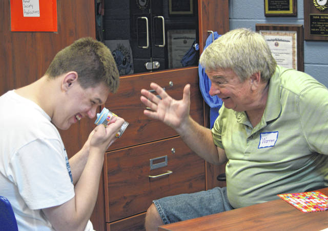 Drew Meyer, left, of Fort Loramie, shares a laugh with camp assistant Warren Shepherd, of Sidney, while making a craft during Shelby County Arc's Summer Recreation Camp 2019. Around 30 campers from every part of Shelby County register for camp each year.