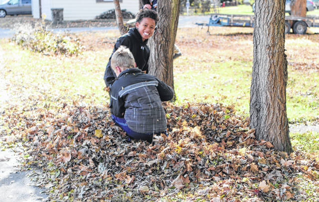 Sidney City Schools students took advantage of having the day of school because of parent-teacher conferences Friday to play in the leaves. Though it was chilly, a game of hide and seek was played in the alley off Water Street. Drew Howell, 8, looks around as he finds Robbie Hubble, 8, in a pile of leaves. Drew in the son of Nicole Osterhout and Ramon Howell, of Sidney, and Robbie is the son of Kelsey Harshberger and Zach Hubble, of Sidney.