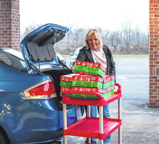 Theresa Chamberlin, of Sidney, unloads the trunk of her car with Operation Christmas Child shoebox gifts Monday at the Sidney Baptist Church. The gifts will be sent to children overseas as part of the Samaritan's Purse program. Gifts may be dropped off at the church, 1322 E. Court St., through Friday from 5 to 7 p.m. and saturday, Nov. 23, from 11 a.m. to 1 p.m., Sunday, Nov. 24, from 2 to 5 p.m. and Monday, Nov. 25, from 8 to 10 a.m.