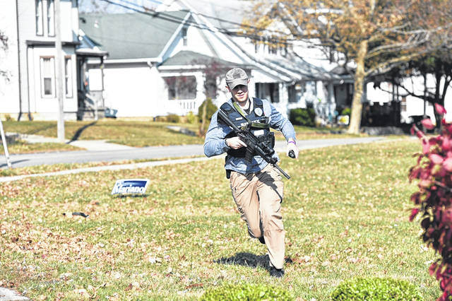 A Sidney Police officer runs to take up position across the street from the house, left, where a person was reported to have a gun on Wednesday, Nov. 6.