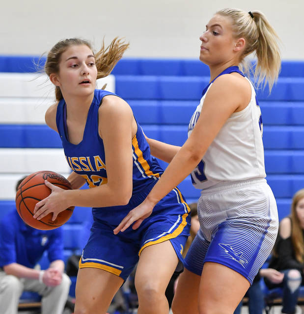 Russia senior forward Jessica York looks to pass while being guarded by Fairlawn's MaCalla Huelskamp during the first half of a Shelby County Athletic League game on Thursday at Fairlawn.