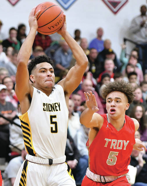 Sidney senior guard Darren Taborn looks to pass with pressure from Troy's Jaden Owens during the first half of a Miami Valley League game on Friday in Sidney. Taborn scored 15 points and had four rebounds.