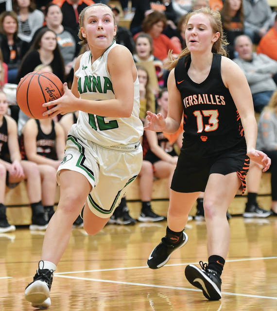 Anna senior guard Michaela Ambos dribbles with pressure from Versailles' Caitlin McEldowney during a nonconference game on Thursday in Anna. McEldowney scored eight points.