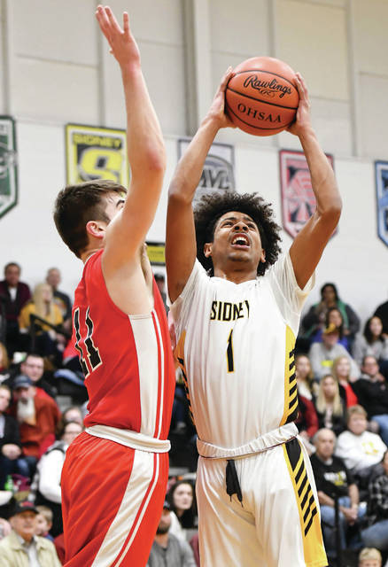 Sidney senior guard Dominick Durr shoots with pressure from Bellefontaine's Maverick Calton during the first half of a nonconference game on Friday in Sidney.