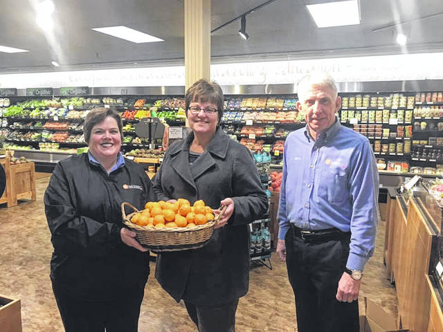 Deli Manager Stephanie Heitkamp, left to right, Diana Russel, Shrine director of Fund Development, and Wally Wagner, owner of Wagners IGA, hold a basket of oranges which will be used at the children's St. Nicholas Celebration on Dec. 7, 2019.