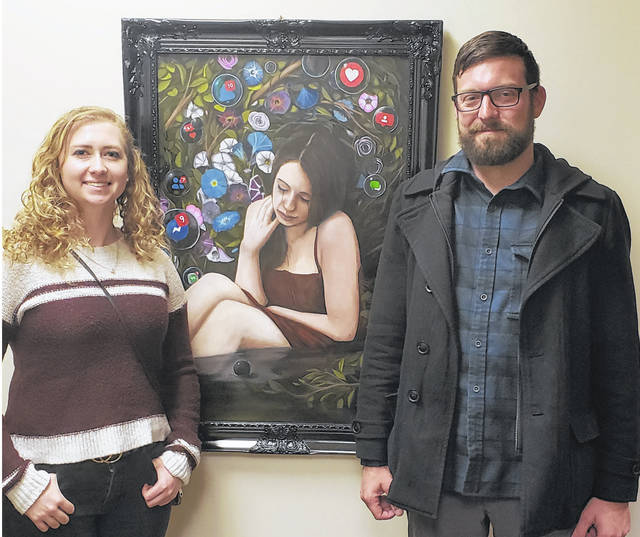 """Emily Artz, left, girlfriend of artist Austin Pearson, right, who painted the artwork entitled """"Social Dysmorphia,"""" are pictured with his painting immediately after it is hung on the wall outside of the Emergency Operations Center/Training Room on the second floor of the Sidney Police Department. The piece won the People's Choice award in the Tri-County Board of Recovery and Mental Health Services' 13th annual Art of Recovery exhibition of paintings, drawings, photography, poetry and music in October."""