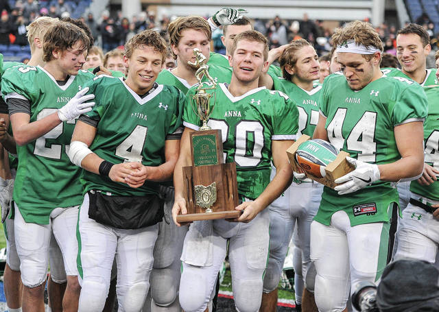 Anna senior running back Riley Huelskamp, center, holds the Division VI state championship trophy while surrounded Bart Bixler, left, Malachi Minnich, right, and other teammates shortly after the team presented with the trophy on Friday at Tom Benson Hall of Fame Stadium in Canton. The squad beat New Middletown Springfield 48-14 to capture the first football title in program history. It's also the first football championship of any Shelby County team. Read more about the game in today's sports section on page 10.