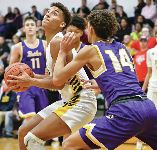 Sidney senior forward Lathan Jones looks to shoot with pressure from Vandalia-Butler's Quincy Rackley during the fourth quarter of a Miami Valley League game on Friday in Sidney. Jones scored nine of his 13 points in the fourth quarter to help the Yellow Jackets rally.