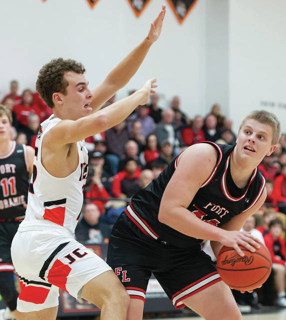 Fort Loramie sophomore guard Nolan Berning looks to pass while being guarded by Jackson Center's Garrett Heitkamp during the first half of a Shelby County Athletic League game on Tuesday in Jackson Center.