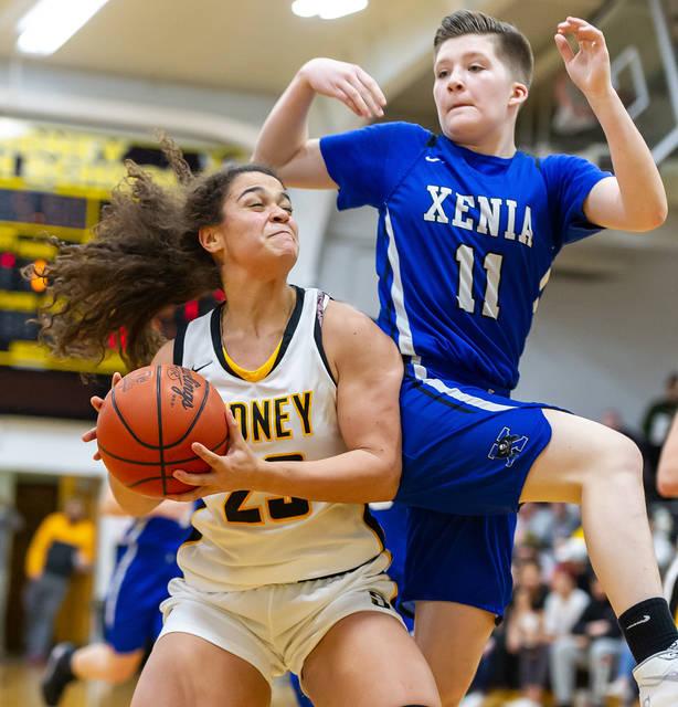 Sidney freshman guard Allie Stockton prepares to shoot while Xenia's Bri Randall collides with her during the first half of a Miami Valley League game on Wednesday in Sidney. Stockton led Sidney with 25 points and is averaging 18.4 points per game.