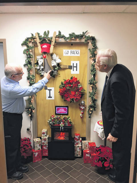 Utilities Director William Blakely talks about the symbolism of the door to his office that he decorated for this year's Christmas Door Decorating Contest as Mayor Mike Barhorst judges the door. His door tied for second place in this year's competition.