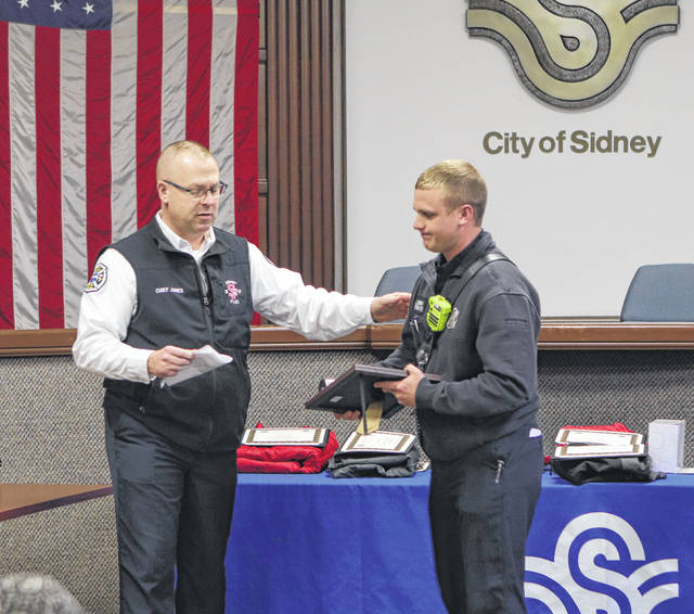 Sidney Fire Chief Brad Jones, left, congratulates Dallas Davis on his 15 years of employment with the city of Sidney. City employees were honored Friday on various milestones of employment.