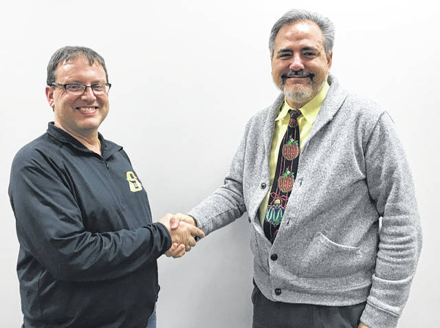 Sidney City Schools Board of Education President Bob Smith, right, thanks outgoing board member Chip Hix for his commitment to the school district.
