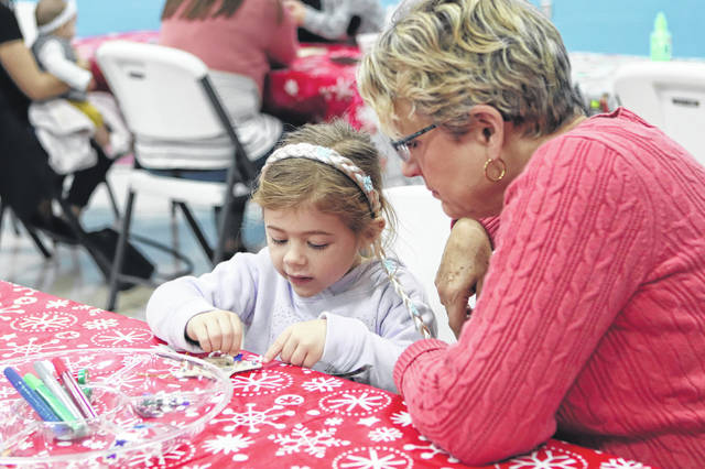 Vivienne Wilson, 4, daughter of Nikki Wilson, of St. Paris, makes Christmas ornaments with her grandma, Kim Janek, of Rosewood, during a Holiday Open House Tuesday morning at the Shelby Hills Early Childhood Center.