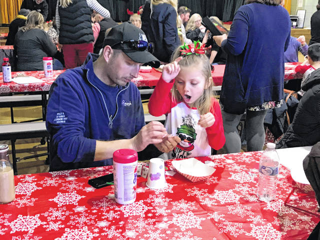 Whittier Early Childhood Center celebrated Christmas a little early as the preschoolers and their parents made crafts and sang songs. Austyn Phillips and her stepdad Darrell Porter, of Sidney, work on a craft together during the event.