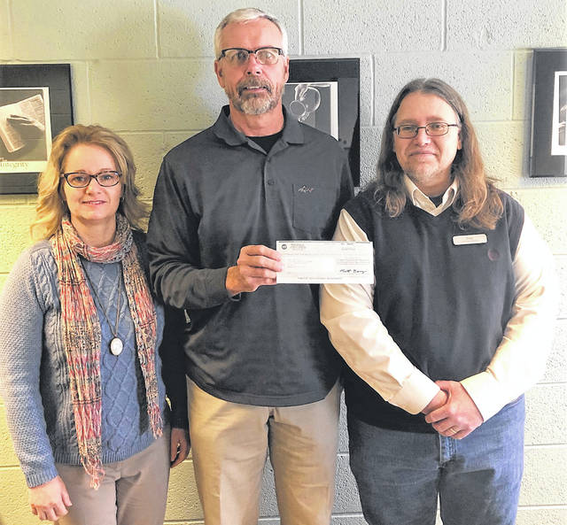 Midwest employees Coreen Ott, left, and Mike Dieringer, center, make a donation to Troy Montgomery of Mercy Unlimited in Wapakoneta.