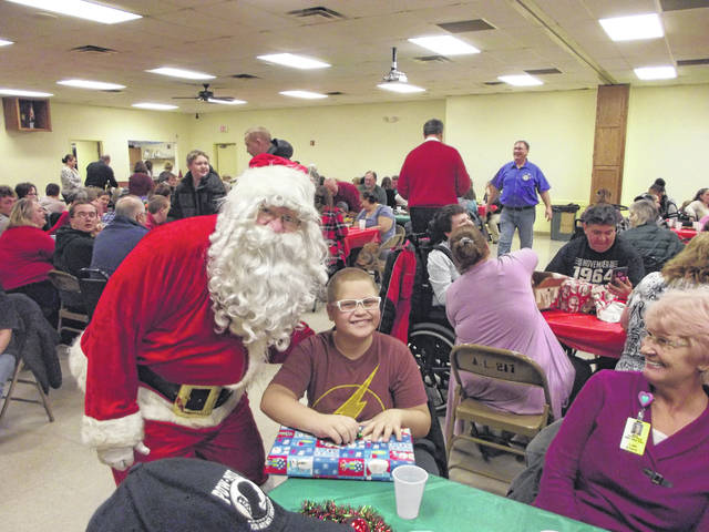 Nathan Martin, 13, of Sidney, son of Shar Klinger and Melvin Martin, receives his present from Santa Claus Monday, Dec. 3, during the annual Rotary Christmas party. This is the 80th year the Rotary has hosted the party. Eighty-four Shelby County students attended the luncheon and party, which was held at the Sidney Veterans Center.