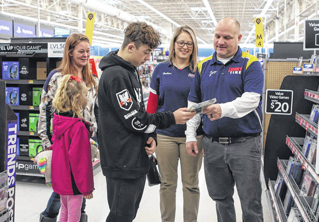"Jeff and Heather Pollar, owners of Best One/Sidney Tire, of Sidney, helps Aiden, 13, son of Jamie and Adam Leugers, of Botkins, pick out a video game at Walmart in Sidney, while Jaime and sister, Brielle 6, looks on behind him. The business sponsored the entire Botkins family, including Aiden's brother Adam, 11, and father, who were also present but not pictured, with money for gifts and food, Saturday morning, Dec. 21, during ""Operation Jingle Bells."" Mantor Auto & Truck Repair, of Sidney, also sponsored April Miller, of Russia, and her six children Saturday."