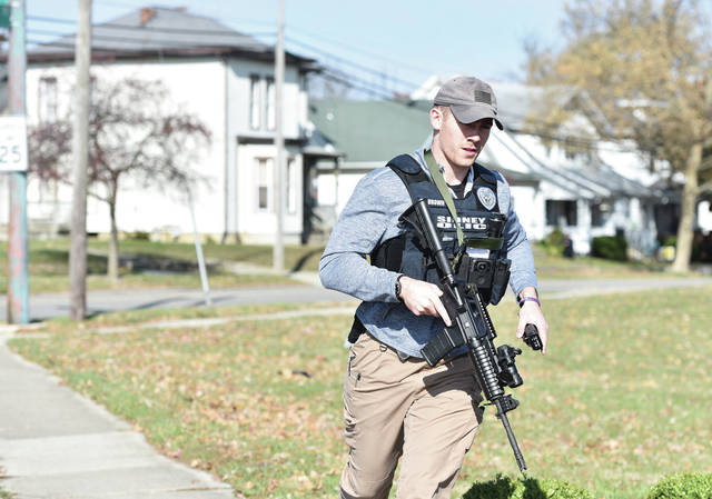 A Sidney Police officer runs to take up position across the street from the house, left, where a person was reported to have a gun on Nov. 6.