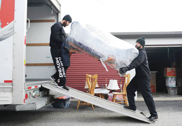 Ricardo Lenhart, left, and Donovan Clark, both of Sidney, load a couch from a storage unit into a moving truck on Saturday, Nov. 16. Both men work for Clark Family Moving.
