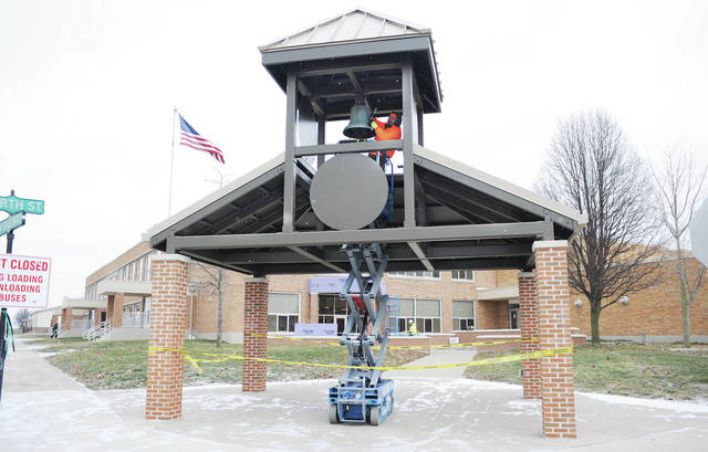 Mike Grooms, of Jamestown, works on the Anna High School bell that AKA Construction attached to a new bell tower in front of the Anna High School and Middle School building on Wednesday, Dec. 11. The bell used to be located on top of the Anna High School and Middle School building before it was relocated to the bell tower. The bell tower is located in front of the new grand school entrance at the south west corner of the school. The old main entrance was located on the south side of the school. Decals will be attached to the bell tower when winter is over because it is too cold for the adhesives to currently work. The bell tower is part of the massive renovations that the school has undertaken. The bell will not be capable of ringing.