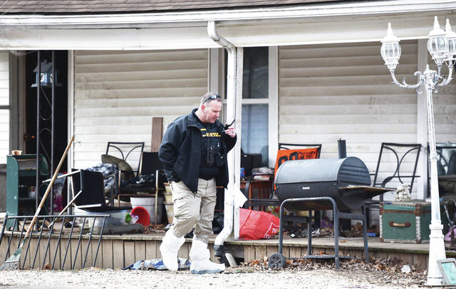 A Sidney Police detective wears bags over his feet as he talks into his phone next to the house he came out of at 701 West North Street between Royan Avenue and North Highland Avenue around 10:45 a.m. on Wednesday, Dec. 11.