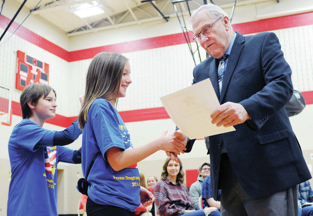 Shelby County Sheriff John Lenhart, hands Alexa Hartle, 10, of Jackson Center, daughter of Shannon and Jason Hartle, a certificate for completing the Shelby County Sheriff's Office D.A.R.E. program during a ceremony at Hardin-Houston Local School on Tuesday, Dec. 10. Standing in line behind Alexa is Joseph Jeffers, 11, of Jackson Center, son of Bobbie Stewart and Jim Watson. Lenhart handed out certificates to students from Jackson Center, Fort Loramie, Hardin-Houston and Botkins. D.A.R.E. essay winners were announced by Shelby County Sheriff's Deputy Brian Strunk.